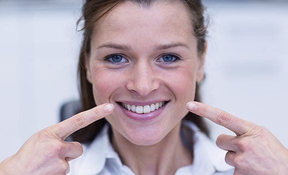 Woman smiling after metal-free dental restoration treatment
