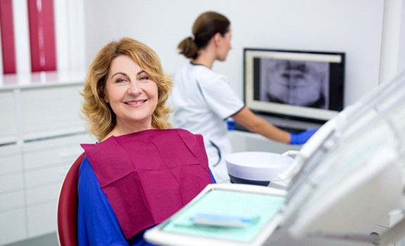 Middle-aged woman smiling while sitting in dental chair