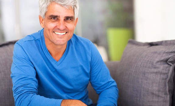 Older man smiling while wearing a blue sweater