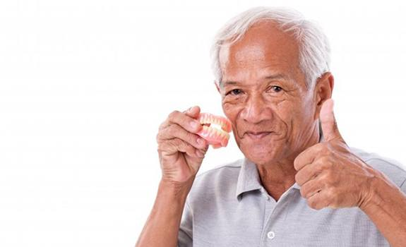Man with dentures in Lakewood gives thumbs up.