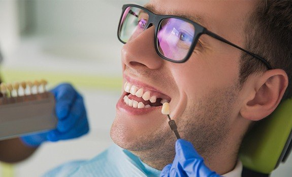Man with missing teeth looking at tooth replacement color options