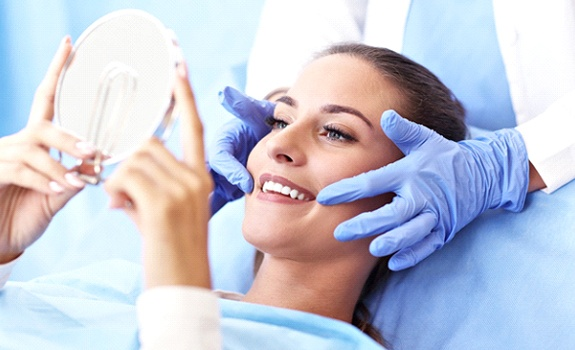 Woman with brown hair getting an Invisalign consultation from her dentist